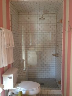 White penny rounds floor and white subway with black grout. Clear glass shower door and bench - MAYBE FOR GUEST BATH? No pink-striped wall paper of course subway tile shower