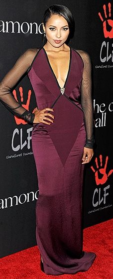 Kat Graham showed off her curves in a body-skimming purple Pamella Roland gown with a plunging neckline and sheer sleeves.