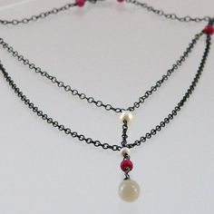 oxydized sterling silver with moonstone, rubies and freshwater pearls.