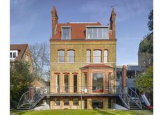 Rear of Victorian villa restoration, metal balcony, contemporary extension, terracotta tiled roof. Full height glazing.