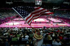 A fan waves the U.S. flag during the men's gymnastics qualification in the North Greenwich Arena in London
