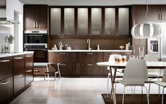 A modern kitchen with brown drawers, doors, glass doors and a dining area with white chairs and dining table with white table top and birch legs.