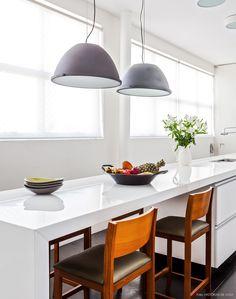 Cozinha minimalista com bancada e armários brancos e banquetas de madeira.