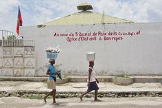 Haitian women walk past the exterior gate of the Court of Law Annex in Croix-des-Bouquets. UNDP, along with the Haitian Government, has created courthouse annexes in order to remedy the lack of access to legal recourse faced by many residents of remote areas.   www.undp.org  Photo: UN/Victoria Hazou