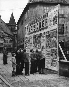 Boys examining circus posters. Photograph by Carl Mydans. Ansbach, Germany, 1954.