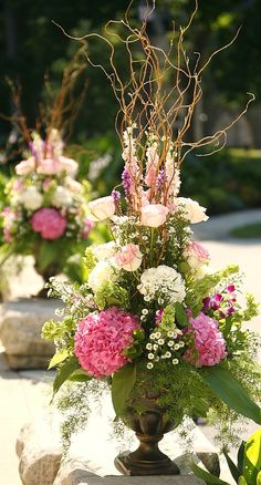 urn arrangements. I love sticks added to arrangments as they remind of woods and gardens and keep flowers from having a very formal or stiff look as well as providing movement and drama to the art.