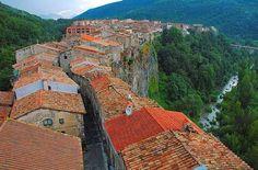 CASTELLFOLLIT DE LA ROCA. Situado en la provincia de Girona, este espectacular y bonito pueblo es uno de los más pequeños de España. El pueblo se asienta sobre una impresionante pared de basalto. La iglesia y las casas cuelgan sobre la pared basáltica al borde del precipicio; esta imagen se ha convertido en una de las más fotografiadas y pintadas de Cataluña. También es un magnífico mirador natural desde el cual se pueden observar los valles colindantes.