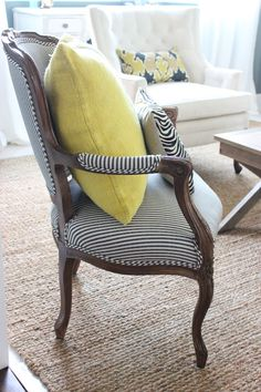Buttercream yellow pillows accent the navy and white striped chairs. Such a fresh look! Turning Oakleaf, a soft buttercream yellow, is PPG's 2014 Color of the Year.