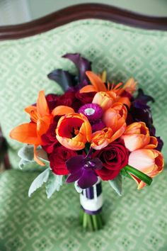Pretty Wedding Bouquet Featuring: Orange Lilies, Orange Tulips, Fuchsia Zinnias, Red Roses, Purple Orchids, Purple Calla Lilies, Dusty Miller & Green Lily Grass Loops