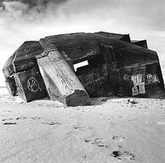 a black and white photograph of a concrete bunker sunk in an angle into a sandy beach