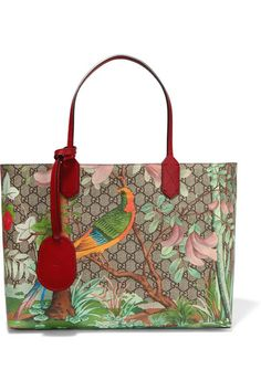"Gucci's coated canvas tote is monogrammed with the label's unmistakable interlocking 'GG' logo. Finished with claret leather handles, this structured style features a painterly floral and bird motif inspired by the ""Chinese landscapes depicted on 18th century tapestries and screens."" The faux suede-lined interior is fitted with a zipped pocket and two card slots."