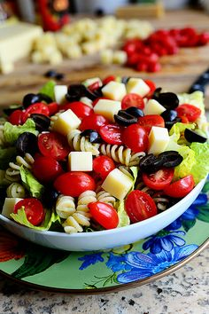 Pesto Pasta Salad with chunks of parmesan cheese, Lettuce, tomatoes, olives & mozzarella cheese