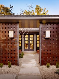 A basket weave metal screen and gate separate the entry courtyard from the front yard. The sconces are by Two Hills Studio.