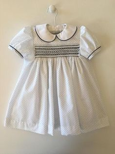 Baby girl smocked dress, soft white fabric tiny navy spots and Peter Pan collar, edged with fine navy piping. Other sizes made to order, also available in white with pink spot, white with light blue spot. Smocked Baby Clothes, Girls Smocked Dresses, Toddler Girl Dresses, Little Girl Dresses, Baby Dress Design, Baby Girl Dress Patterns, Pregnancy Fashion Winter, Smoking, Girlie Style