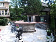Photo by Dennis Miller. Outdoor kitchen with natural stone base and poured concrete countertop.