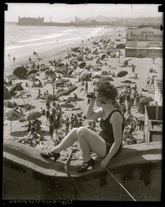 Flapper look-out at Santa Monica, CA beach (c. 1920). Original Pacific Ocean Park can be seen in background.