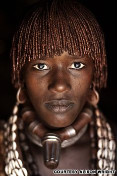 """Goite from the Hamer Tribe, Omo Valley, Ethiopia, 2006  """"I was photographing this woman's husband as he was piercing their cow in the neck with an arrow and bleeding him to mix with milk, a high source of protein in their diet. I turned and she was staring from the dark of her hut.""""    http://travel.cnn.com/face-face-portraits-human-spirit-046291?iid=article_sidebar#"""
