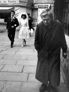 Alfred Eisenstaedt - Elderly woman walking along street while bride and groom walk behind, Paris, 1963.