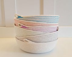 This fun and original rope pot was partially dyed a navy blue on the bottom half and the top boasts randomly wrapped section of happy, brightly colored cotton tread. It has a lovely lid topped with an unfinished wooden knob for a handle.  Use it in the bathroom for hair supplies, or toiletries. Keep it on a bookshelf, or use it to stash away the kids crayons and colored pencils. The possibilities ae endless!  Spot clean with soap and water.  Basket Dimensions: 8 inches tall 9 inches in…