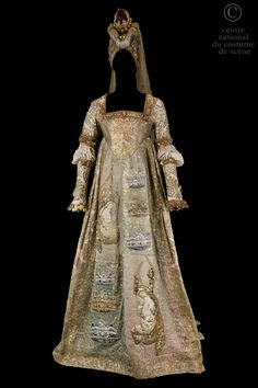 Queen..Renaissance dress in beige and beige sateen down, all painted gold motifs. Square neckline trimmed with a gold band molded latex; tall with a rounded tip effect. Front panel trimmed with pink applications, blue, gold, silver lace forming crowns and religious grounds. Bubbled in unbleached linen sleeves. Hennin lame old gold, topped with a gold lamé bead and fantasy motifs, golden crown adjoining ecru tulle veil embroidered with gold leaf.