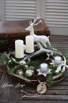 Ein Adventskranz aus Naturmaterialien wie Moos, Rinde, Rebe, Flechten, Zapfen und Lebensbaum. Die Mitte ziert ein Geweih aus silbernem Metall, auf das man zwei Kerzen stellen kann, zwei...