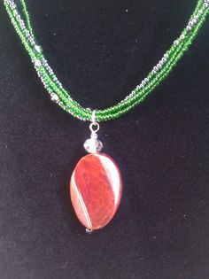 Green multi-strand necklace with red amber accent