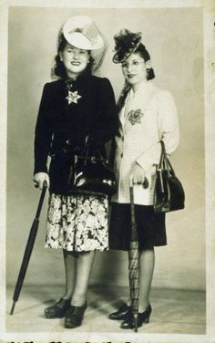 """Two well-dressed women wearing Jewish stars pose holding umbrellas.  Pictured on the right is Simone (Grynberg) Finifter. The photo, which is inscribed to her daughter, Rachel, reads: """"Your mother, who suffers a lot."""""""