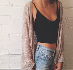 Black strappy crop top, light wash high-waisted shorts and a tan cable-knit cardi