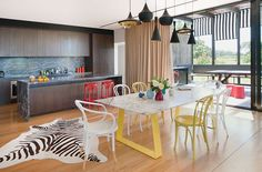 In this Australian home, classicTom Dixonpendant lampscontrast witha bright dining table setup.