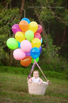 Baby with a bunch of colorful helium balloons.  Adorable.