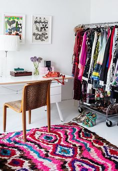 A cheetah patterned chair and colorful Moroccan rag rug are tempered by the simplicity of a white table and lucite lamp, inside Irene Neuwirth's crazy colorful home.