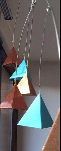 Das Weihnachtsmobile hatte seine Dienste getan und sollte nun von den Glaskugeln befreit frischen Wind ins Wohnzimmer bringen. Mit dreiseitigen Pyramiden aus farbigem Papier ist das recht gut gelungen. Mehr dazu findet ihr bei LILAMALERIE.DE
