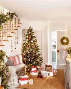 Recibidor decorado de Navidad con árbol con adornos en blanco, cristal y rojo