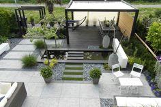 Pond pequeno pero completo con plantas (notar en las esquinas las altas y graminaceas en el exterior) y adornos en simetria, passatoia de piedras y cascada en la pared.