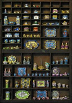 love this cabinet filled with teeny tiny pottery pieces....