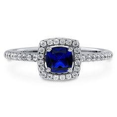 This halo ring is the epitome of elegance with its deep color and dazzling stones. Made of rhodium plated fine 925 sterling silver. Features 0.46 carat cushion cut simulated blue sapphire cubic zirconia (5mm) in 4-prong setting. Accented with 0.18 carat round cut CZ in micro pave setting. Band measures 1.6mm in width. Nickel free.