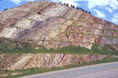 Tilted Rock LayersColorado | #Geology #GeologyPage The sedimentary layers in this large roadcut near Denver Colorado. can be clearly recognized by the variation in color. These layers can be recognized as having been deformed because they have been tilted so they are dipping to the east (the left side of photo). This deformation was related to the uplift of the Rocky Mountains. Photo Copyright University of Mount Union Geology Page www.geologypage.com