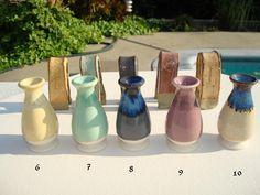 Coyote glaze testing. Front row: Cone 6 white porcelain slip cast vases. Back…