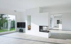 Offener Wohnraum mit Kamin (de Skandella Architektur Innenarchitektur)