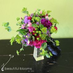 Bridesmaid's bouquet of ageratum, purple carnations, green hypericum berries, and globe amaranth by Beautiful Blooms by Jen.