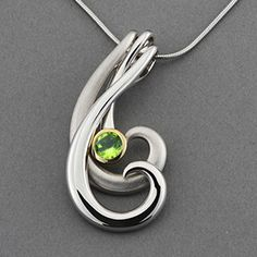 Two free flowing silver ribbons swirling with a peridot framed in yellow gold makes this piece both unique and stylish. This piece was made by Joryel Vera and uses both high polish and matte finish fo