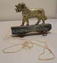 """Late 1800's Early American Tin spaniel pull toy. All original. Dog and base, tin. Wheels, cast metal. 6.5"""" long and 5.25"""" tall. (hulabar/eBay)"""
