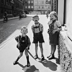 Three children on a sidewalk in an unknown German city having fun with the photographer Bill Perimutter