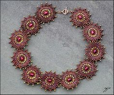 """Burgundy and Lace by Ellygator 16"""" length, red sweetwater pearls, gold lustre size 15 seed beads, burgundy metallic and gold lustre size 11 seed beads, matte burgundy and gold triangle beads, nylon thread, cold-filled sterling crimps, jump-rings and closure finding.  This piece is done in circular brick stitch around each of the central pearls. I (the artist) finished each circle with a picot edge and then sewed them together for a necklace."""