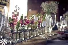 Vintage barn wedding tablescape featuring single stems of spring flowers in pinks, blush pink and white.  Flowers by Buckeye Blooms    Photo by Inspirations by Amy