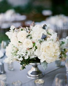 Lush arrangements of garden roses, ranunculus, sweet peas, snowberry bush, and astilbe decorated every tabletop.