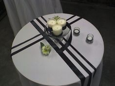 Black and white tablescape with candles on small cake plate, votives with tealight and black rice, tealight holder as a vase by #WhidbeyPartyGirls.