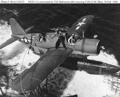 """Carrier Raids on Truk, 17-18 February 1944: Vought OS2U-3 """"Kingfisher"""" is recovered USS Baltimore (CA-68) after she had rescued Lit JG, George M. Blair from Truk Lagoon, 18 February 1944. Plane's pilot is Lt JG Denver F. Baxter. His radioman, ARMC Reuben F. Hickman, is on the wing, preparing to attach the plane so it can be hoisted on board.Blair's F6F """"Hellcat"""", of Fighting Squadron Nine from USS Essex (CV-9), had been shot down during the dawn fighter sweep over Truk."""