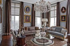 For the living room of an American couple's Paris apartment, Jean-Louis Deniot employed glittering chandeliers, and a small museum's worth of antique portraits.