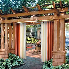 curtains added to pergola built along fence line.  Give privacy from the edge of lawn, rather than closing patio in.